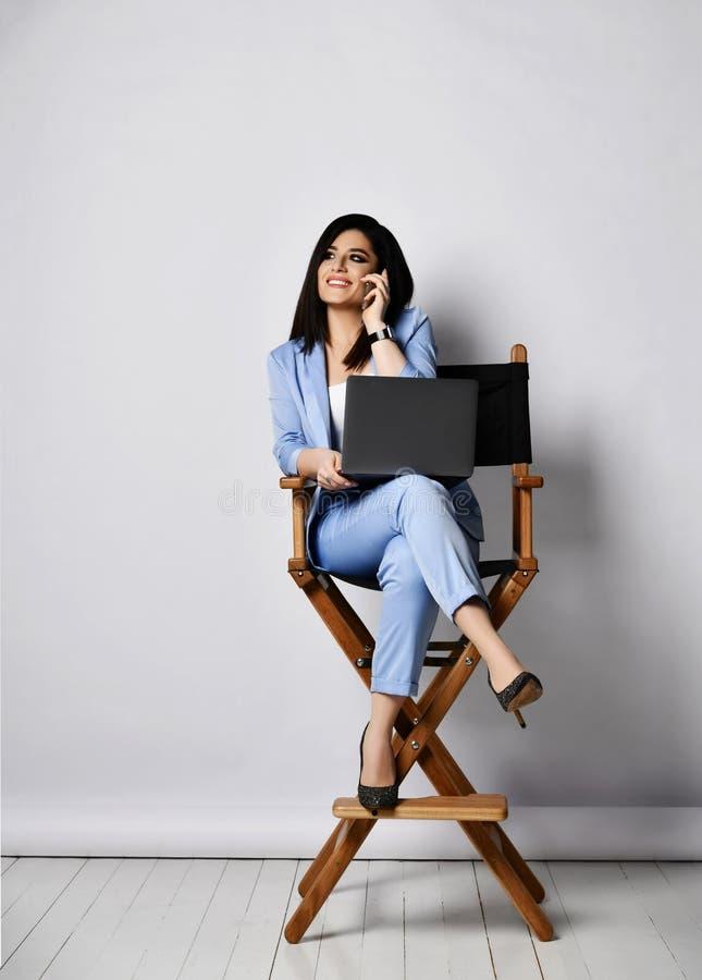 Mujer de negocios sonriente en traje oficial y los zapatos de tacón alto que se sientan con el ordenador portátil en la butaca y  fotografía de archivo