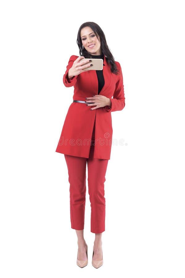 Mujer de negocios sonriente feliz en el traje rojo que toma la foto del selfie que mira la cámara del teléfono foto de archivo libre de regalías
