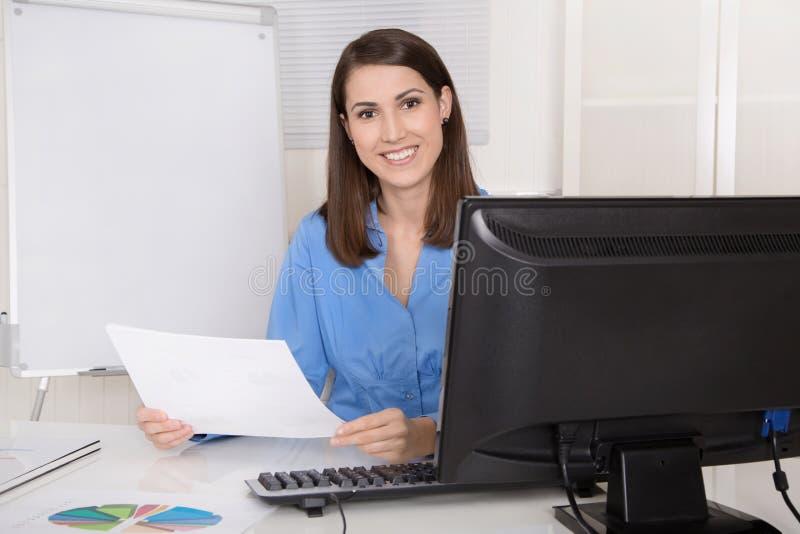 Mujer de negocios sonriente joven acertada que se sienta en su oficina imágenes de archivo libres de regalías