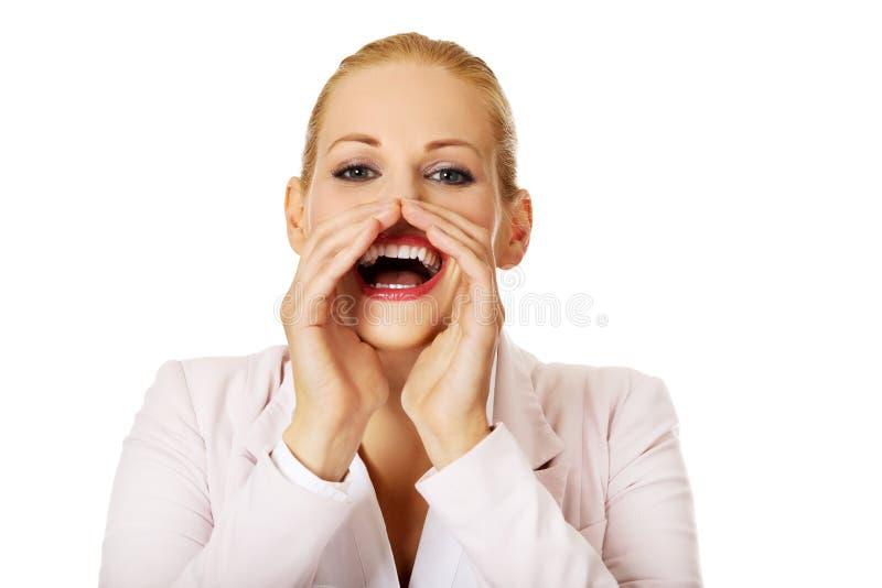 Mujer de negocios sonriente joven que grita ruidosamente o que llama alguien fotos de archivo