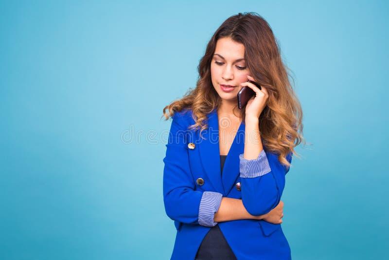 Mujer de negocios sonriente joven que habla oh el teléfono, en fondo azul foto de archivo