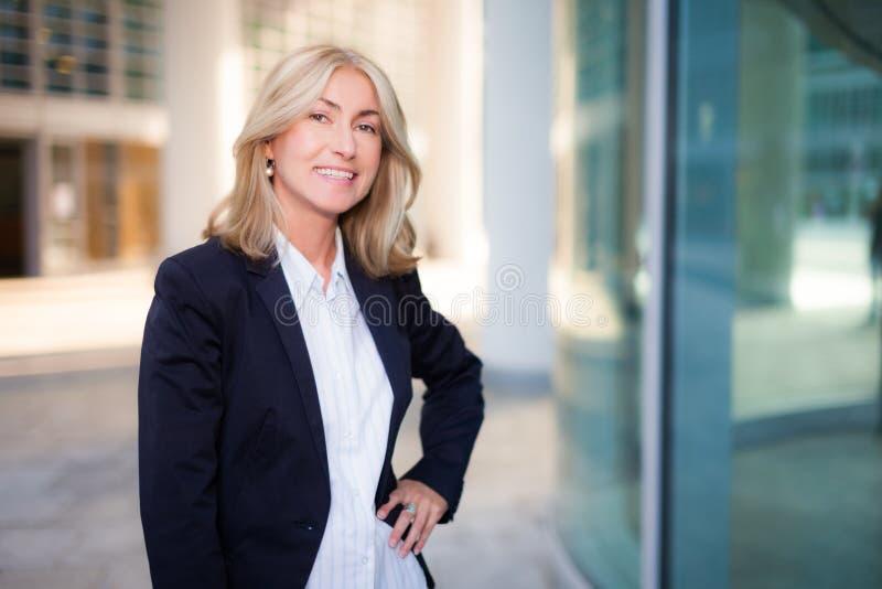 Mujer de negocios sonriente que se coloca al aire libre fotos de archivo
