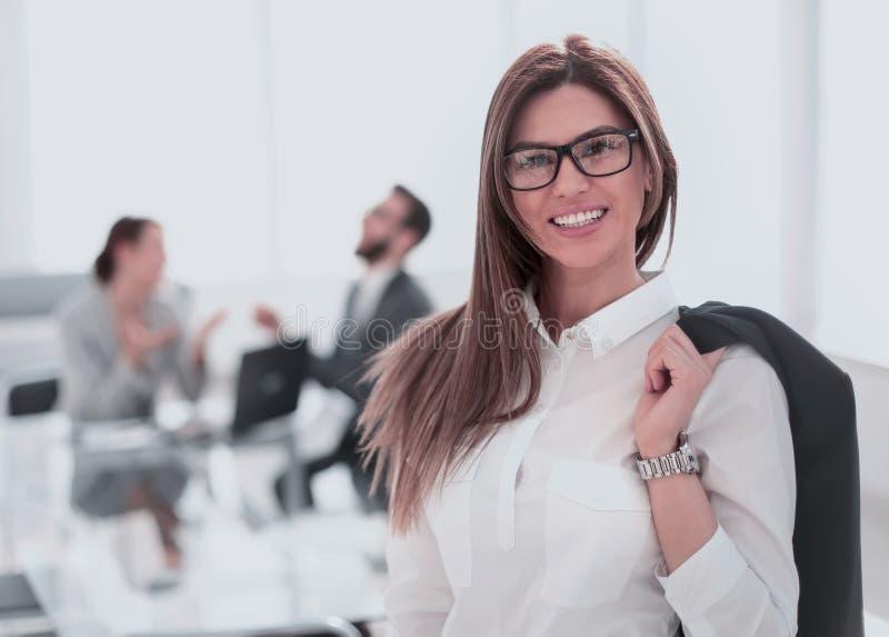 Mujer de negocios sonriente que se coloca con una chaqueta sobre su hombro fotos de archivo