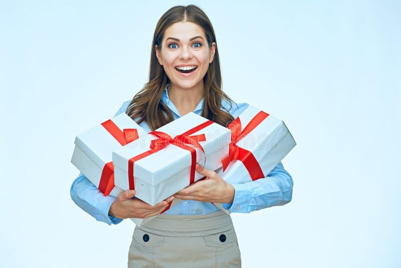Mujer de negocios sonriente que sostiene el manojo de regalos con las cintas rojas foto de archivo
