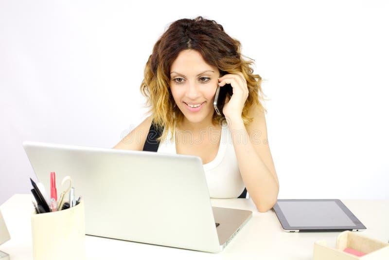 Mujer de negocios sonriente que trabaja con la PC que habla en el teléfono imagen de archivo libre de regalías