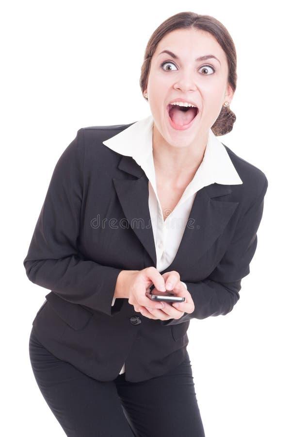 Mujer de negocios sorprendida, emocionada y feliz que manda un SMS en smartphon imagen de archivo