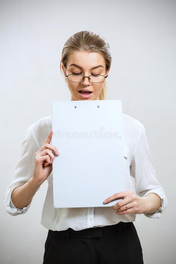 Mujer de negocios sorprendida joven que mira en carpeta fotografía de archivo