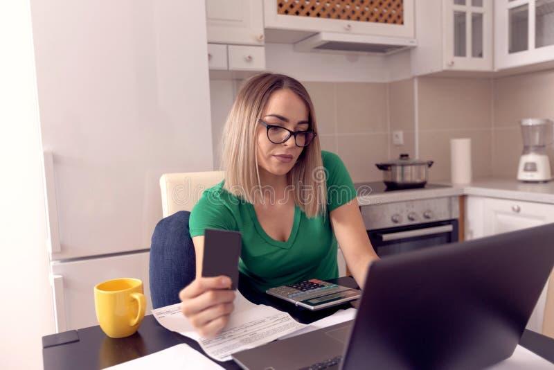 Mujer de negocios subrayada en casa que trabaja - cuentas que pagan fotos de archivo libres de regalías