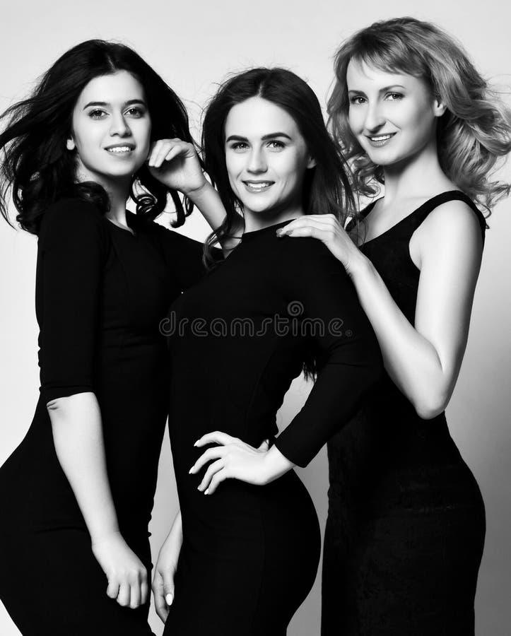 Mujer de negocios tres en los vestidos negros que tienen sonrisa de la diversi?n fotos de archivo libres de regalías