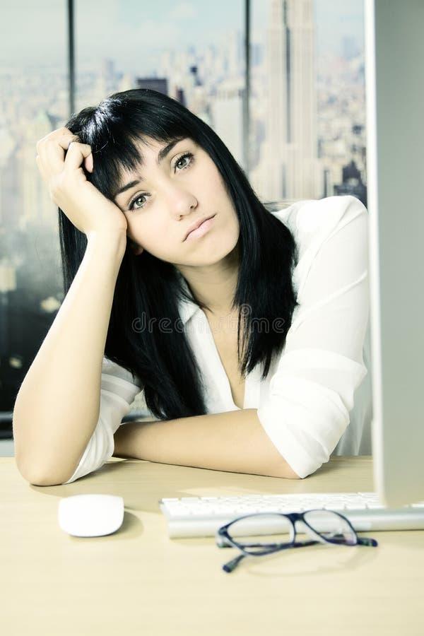 Mujer de negocios triste joven linda en la oficina que mira la cámara fotos de archivo libres de regalías