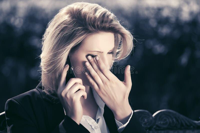 Mujer de negocios triste que invita al teléfono celular en parque de la ciudad fotografía de archivo