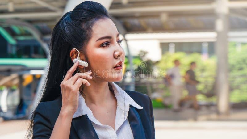 Mujer de negocios usando el auricular al aire libre en ciudad foto de archivo