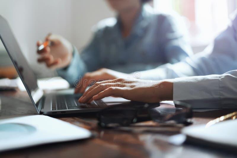 mujer de negocios usando la mano del ordenador portátil que mecanografía en el teclado para encontrar al equipo en oficina Concep fotos de archivo libres de regalías