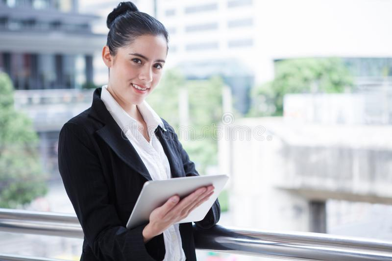 Mujer de negocios usando la tableta digital fuera de la oficina muchacha hermosa joven feliz que trabaja en los medios sociales a imagen de archivo