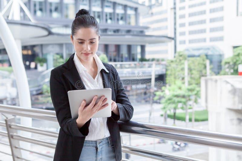 Mujer de negocios usando la tableta digital fuera de la oficina muchacha hermosa joven feliz que trabaja en los medios sociales a fotos de archivo libres de regalías