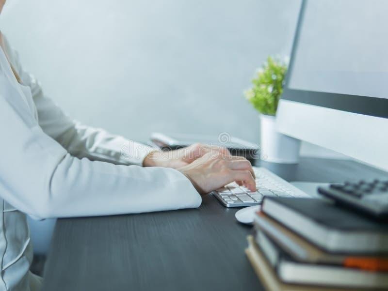 Mujer de negocios usando un ordenador en la tabla negra en la oficina imagenes de archivo