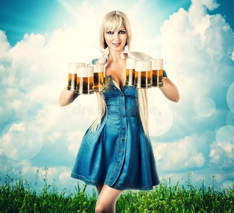 Mujer de Oktoberfest con seis tazas de cerveza foto de archivo