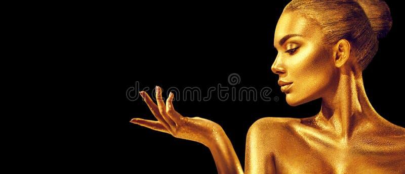 Mujer de oro Muchacha del modelo de moda de la belleza con la piel de oro, el maquillaje, el pelo y la joyería en fondo negro foto de archivo libre de regalías
