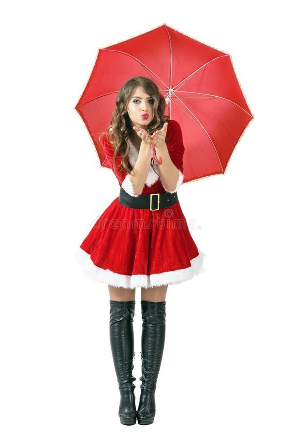 Mujer de Papá Noel bajo beso del aire del paraguas que sopla en la cámara imagen de archivo