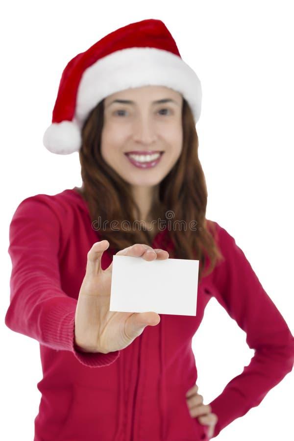 Mujer de Papá Noel que muestra la tarjeta de la muestra foto de archivo