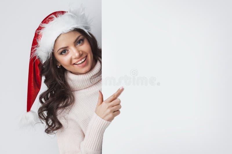 Mujer de Papá Noel que señala en el whiteboard en blanco imágenes de archivo libres de regalías