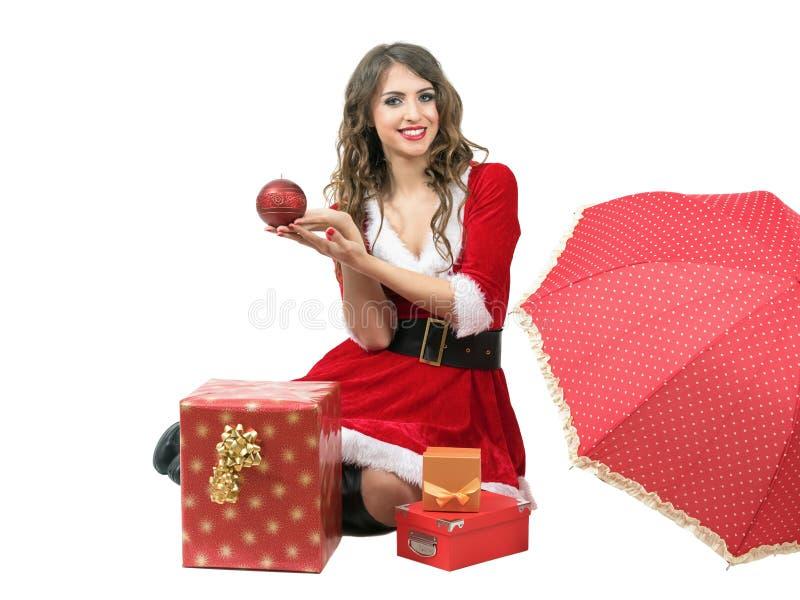 Mujer de Papá Noel que sienta y que lleva a cabo la vela con las cajas del paraguas y de regalo foto de archivo