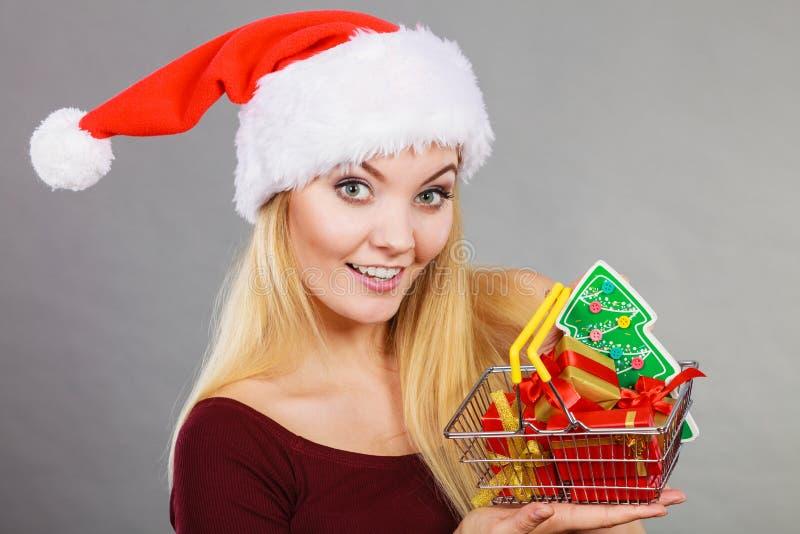 Mujer de Papá Noel que sostiene el carro de la compra con los regalos de la Navidad imagenes de archivo