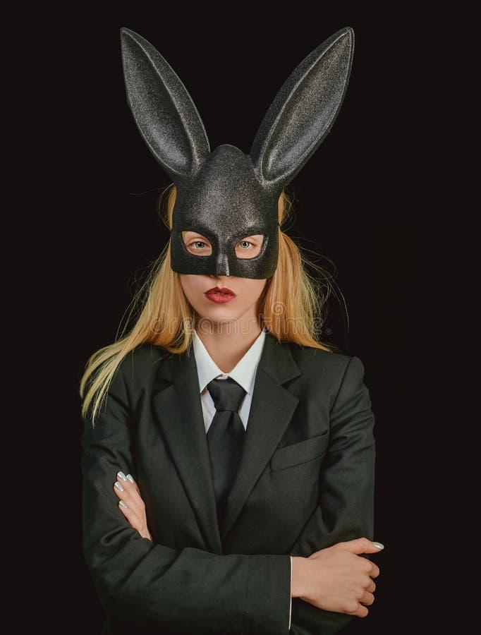 Mujer de Pascua Mujer atractiva con el conejito de pascua de la máscara en un fondo negro y miradas muy sensual Mujer feliz en co imagenes de archivo