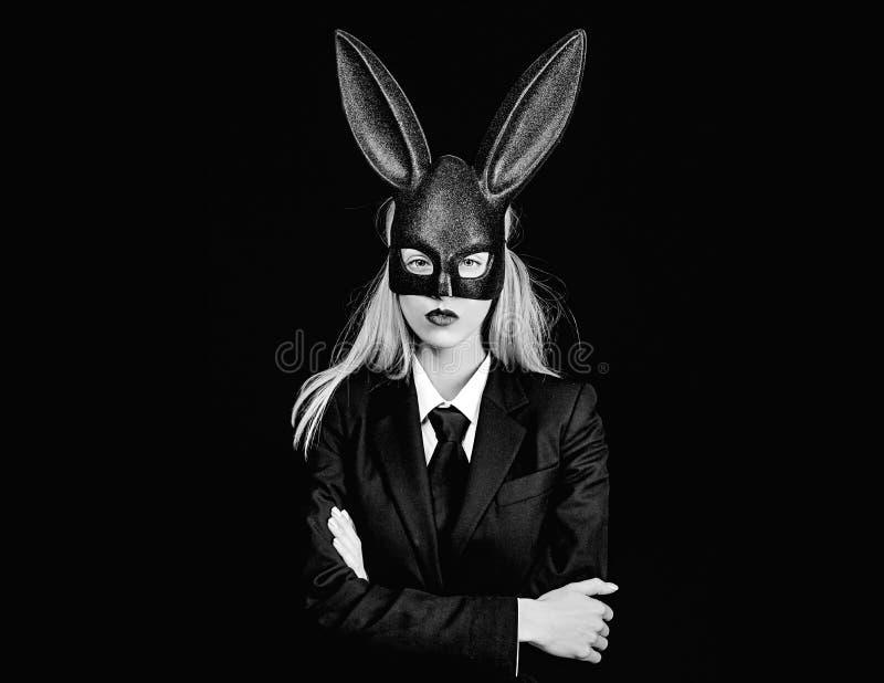 Mujer de Pascua Mujer atractiva con el conejito de pascua de la m?scara en un fondo negro y miradas muy sensual Mujer feliz en co foto de archivo