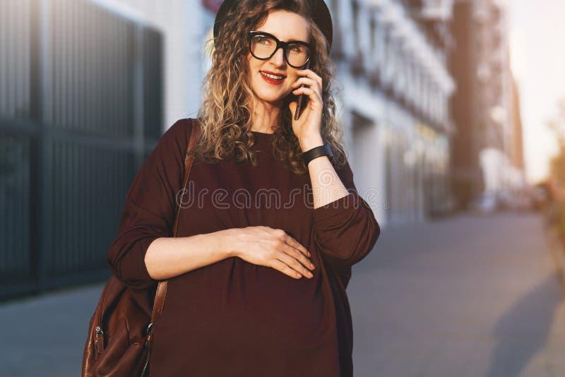 Mujer de Pegnant en vidrios de moda, paseos del sombrero en la calle de la ciudad y negociaciones sobre el teléfono móvil mientra imágenes de archivo libres de regalías