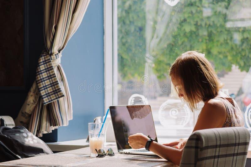 Mujer de pelo corto joven que usa el ordenador portátil en café fotografía de archivo