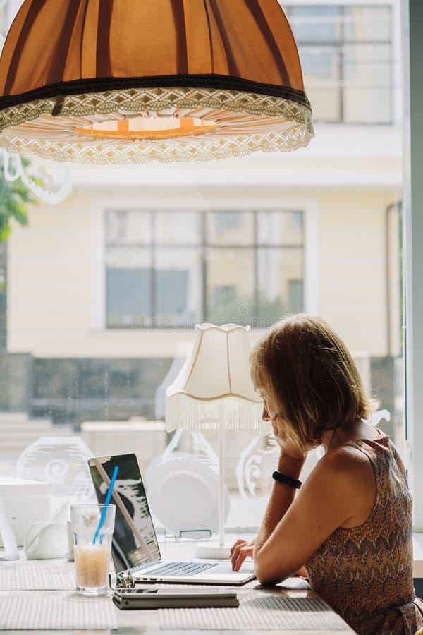 Mujer de pelo corto joven que usa el ordenador portátil en café imagen de archivo