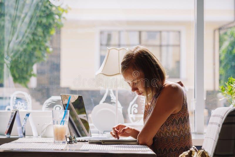Mujer de pelo corto joven que usa el ordenador portátil en café fotografía de archivo libre de regalías