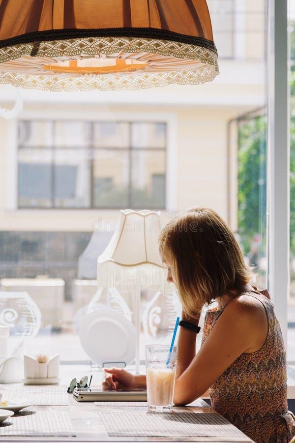 Mujer de pelo corto joven que usa la tableta en café fotografía de archivo libre de regalías