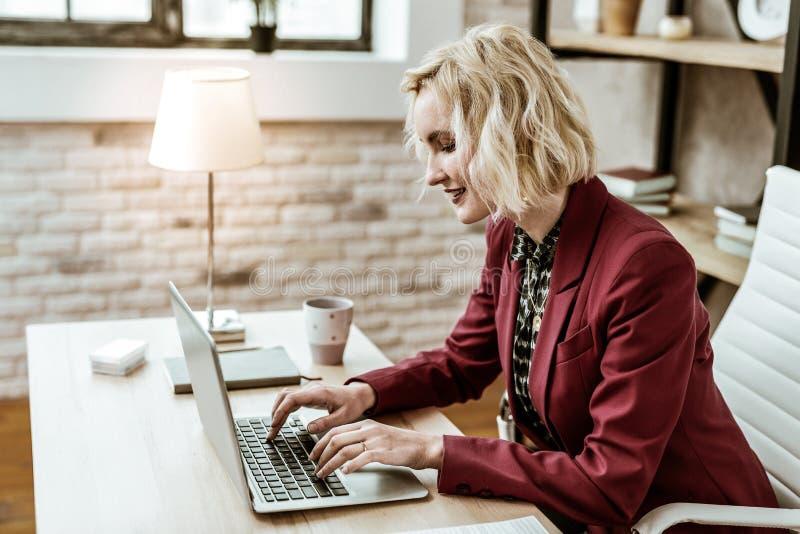 Mujer de pelo corto positiva sonriente que es centrada en crear email foto de archivo libre de regalías