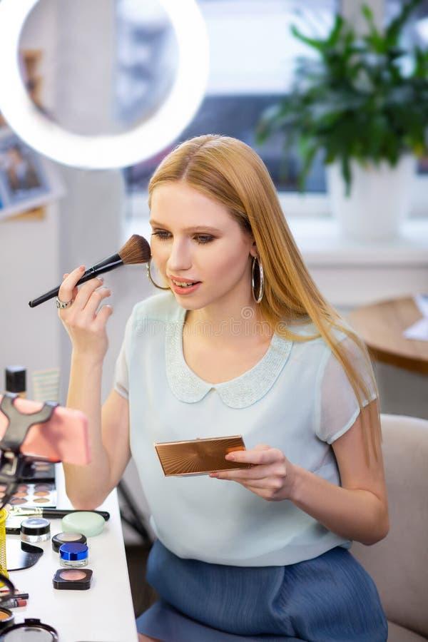 Mujer de pelo largo bonita que aplica el polvo facial fotografía de archivo libre de regalías