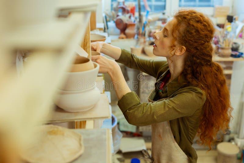 Mujer de pelo largo curiosa que toma el pote de arcilla de un estante m?s alto imágenes de archivo libres de regalías