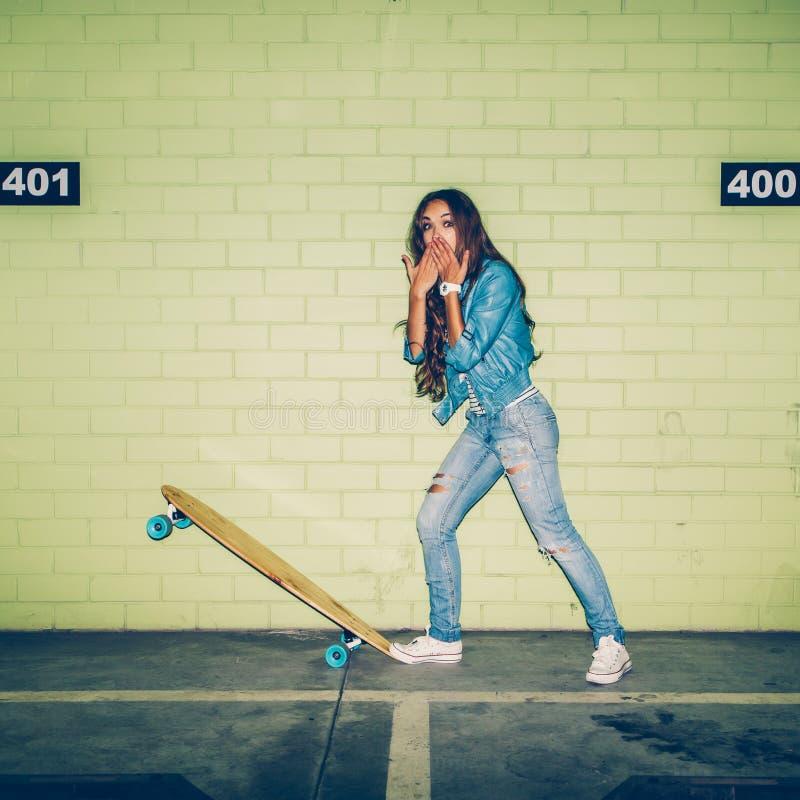 Mujer de pelo largo hermosa con un monopatín de madera cerca de un gree foto de archivo libre de regalías