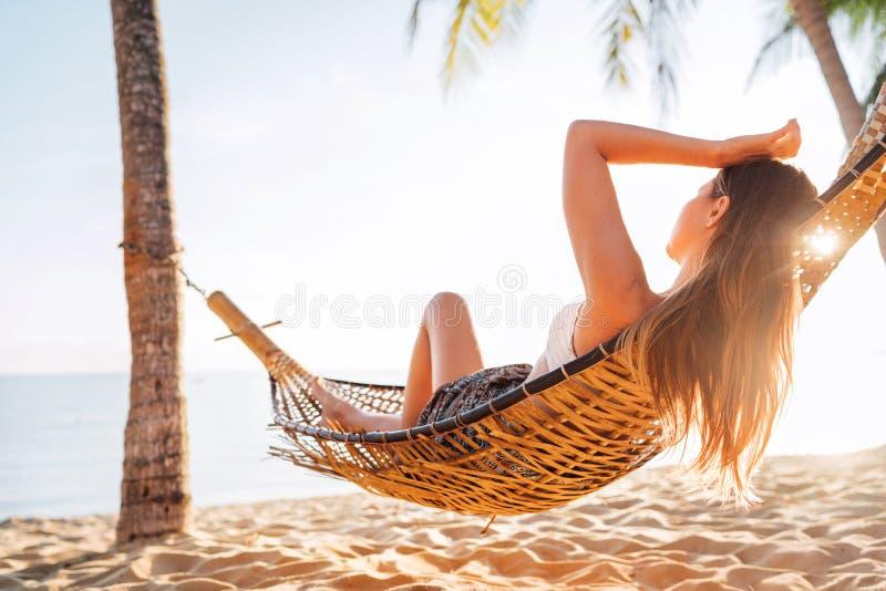 Mujer de pelo largo hermosa joven relajarse en hammok en la playa de la arena imagenes de archivo