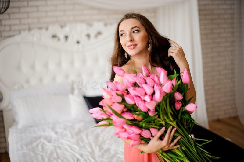 Mujer de pelo largo hermosa que se sienta en la cama con el ramo de tulipanes imagenes de archivo
