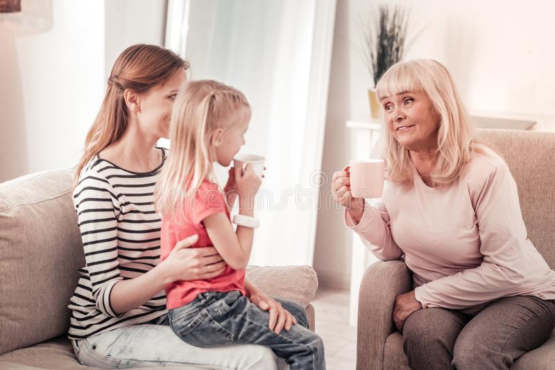 Mujer de pelo largo hermosa que tiene una charla caliente con su madre imagen de archivo