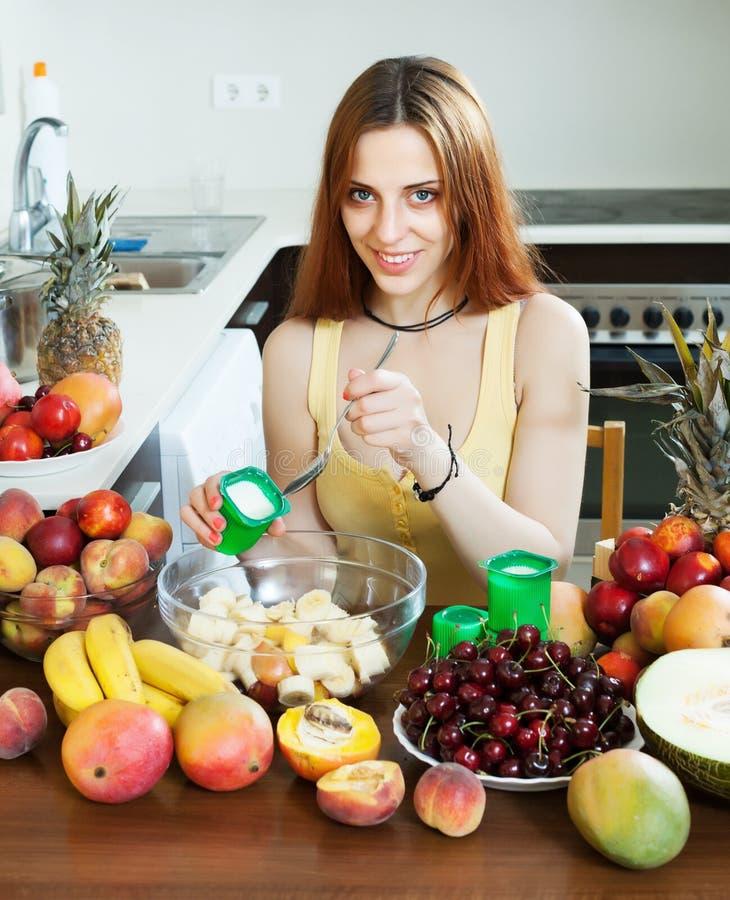 Mujer de pelo largo positiva que cocina la ensalada de fruta imágenes de archivo libres de regalías