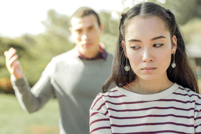 Mujer de pelo oscuro del trastorno que es cansada de su novio celoso foto de archivo libre de regalías