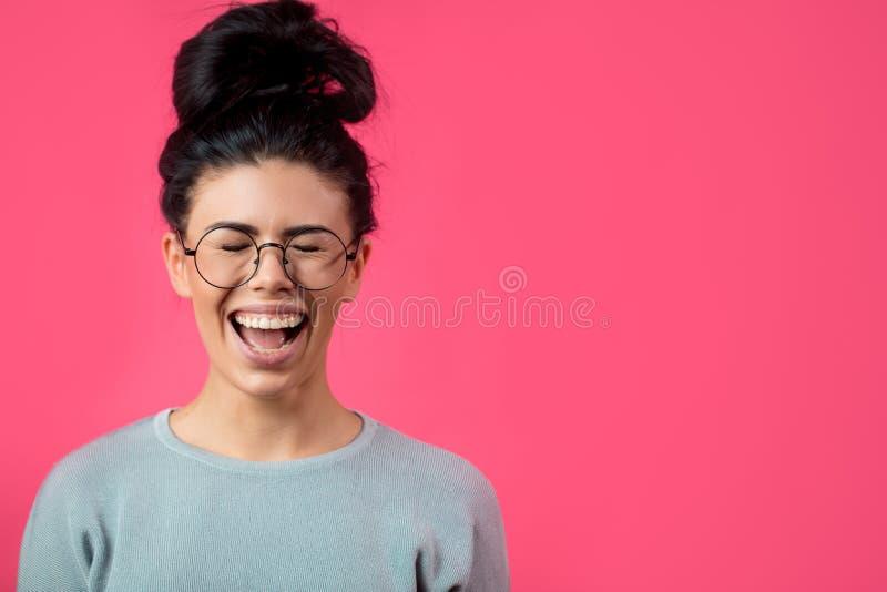 Mujer de pelo oscuro joven de grito y gritadora aislada en el fondo rosado imagen de archivo