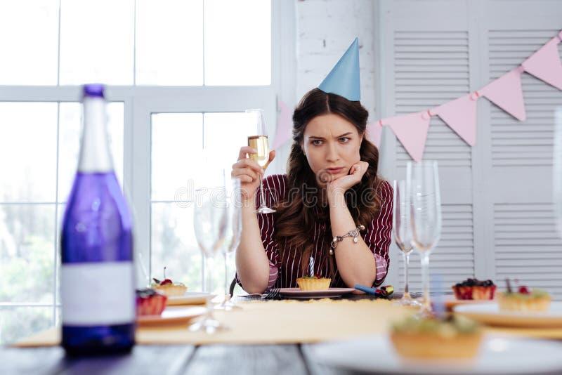 Mujer de pelo oscuro que siente atenta mientras que bebe el champán imágenes de archivo libres de regalías