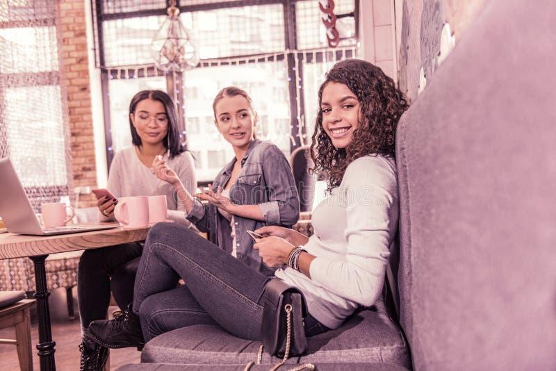 Mujer de pelo oscuro rizada de emisión que se sienta en el sofá gris en cafetería con sus amigos imágenes de archivo libres de regalías