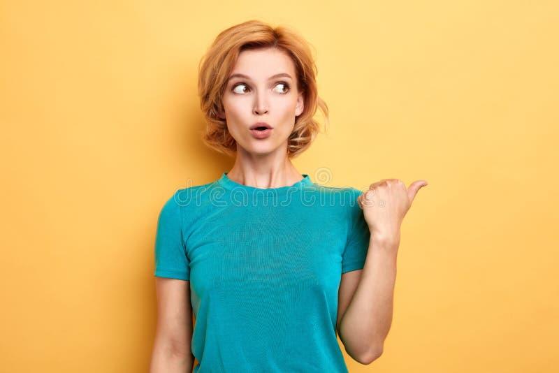 Mujer de pelo rubio emocional sorprendente que señala al lado fotografía de archivo libre de regalías