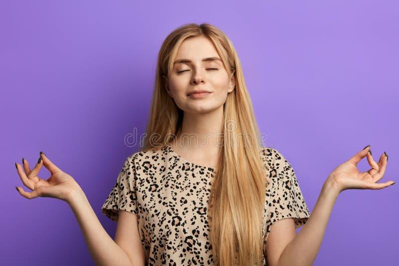 Mujer de pelo rubio vestida en la blusa ligera que mantiene ojos cerrados durante yoga imagenes de archivo