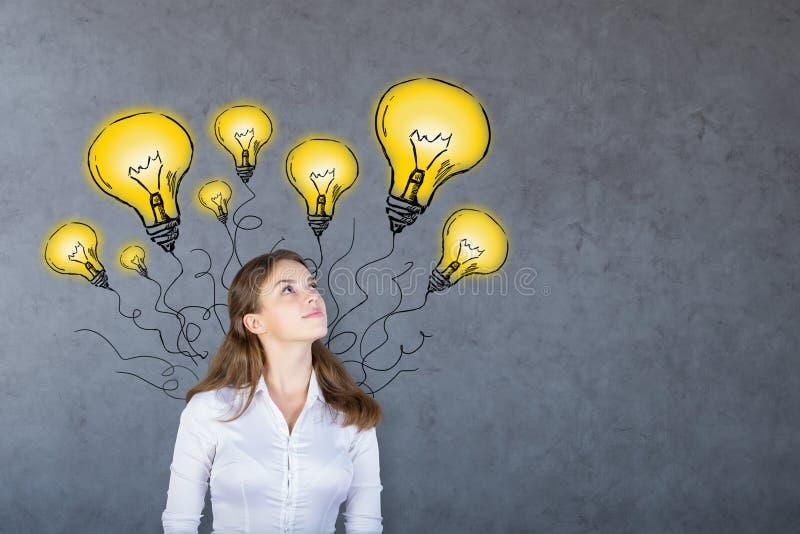 Mujer de pensamiento con las lámparas foto de archivo libre de regalías