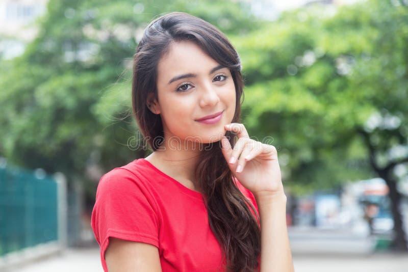Mujer de pensamiento en una camisa roja al aire libre en un parque imagen de archivo libre de regalías